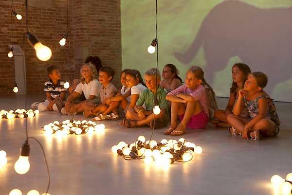 bambini guardano istallazioni di luci