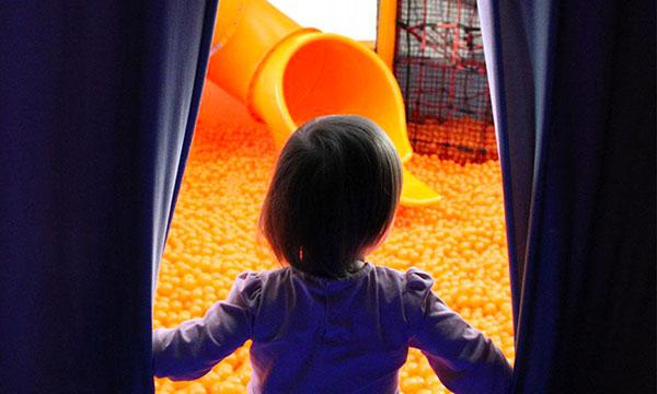 bambina di spalle davabnti a piscina di palline arancioni