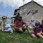famiglia seduta su un prato in montagna Veneto