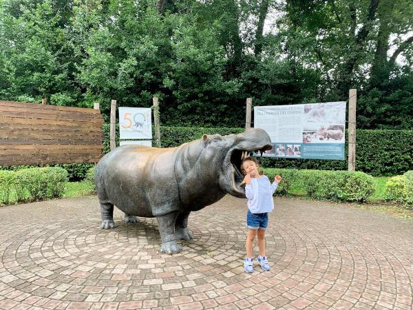 bambina con statua di ippopotamo